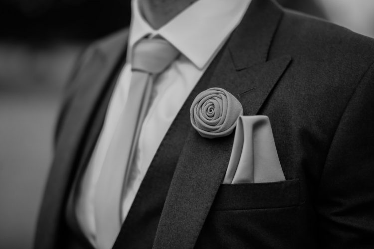 A man with a tie, lapel flower and pocket square.