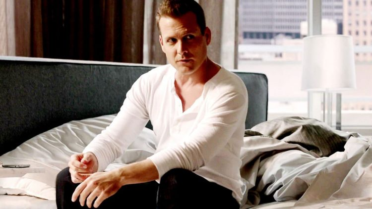 Harvey Specter sitting on a bed in a henley.