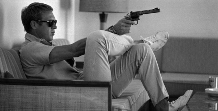 The best men's trainers worn by Steve McQueen sitting pointing a gun.