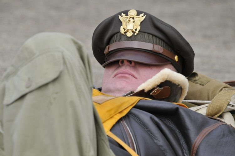 An army man sleeping with his cap on his face.