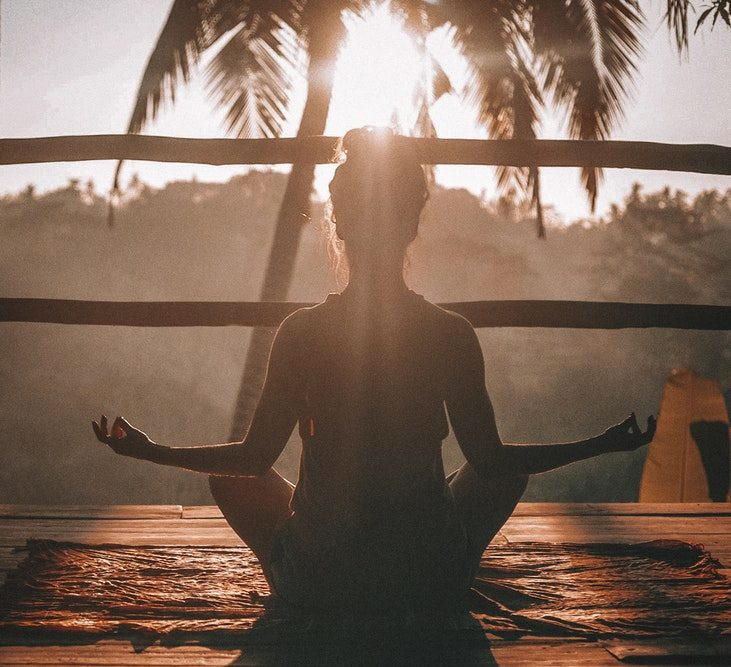Woman doing yoga, focusing is her reason to wake up early.