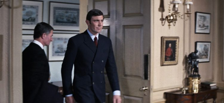 George Lazenby walking in a double breasted navy blazer.