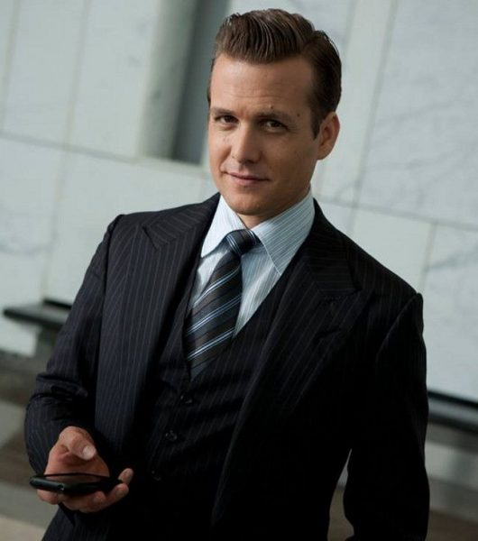 Harvey smiling in a striped suit.