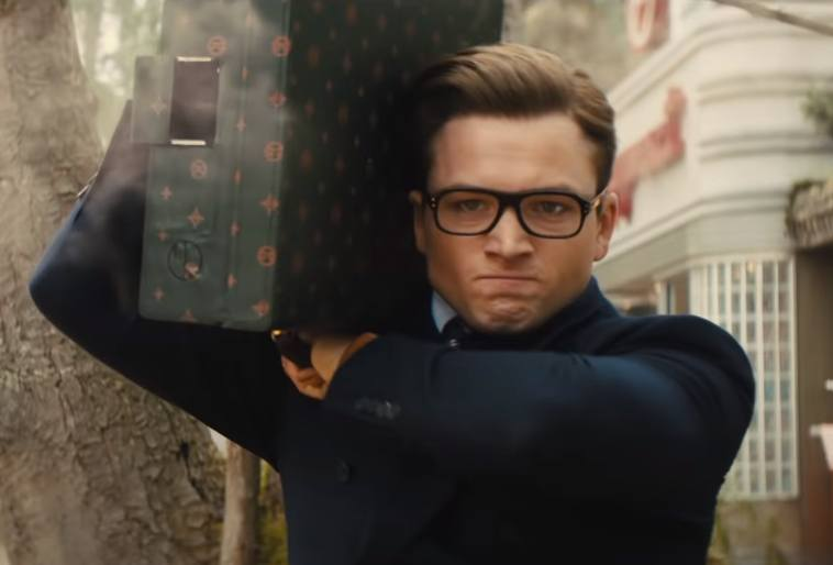 Eggsy holding a missile shooting briefcase