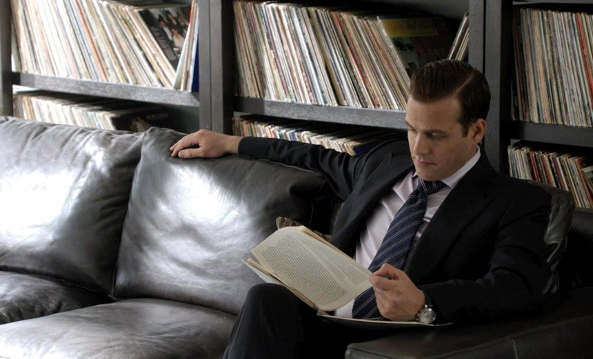 Harvey Specter sitting in front of his badass record collection.