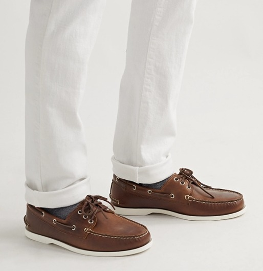 A man wearing brown leather boat shoes with chinos