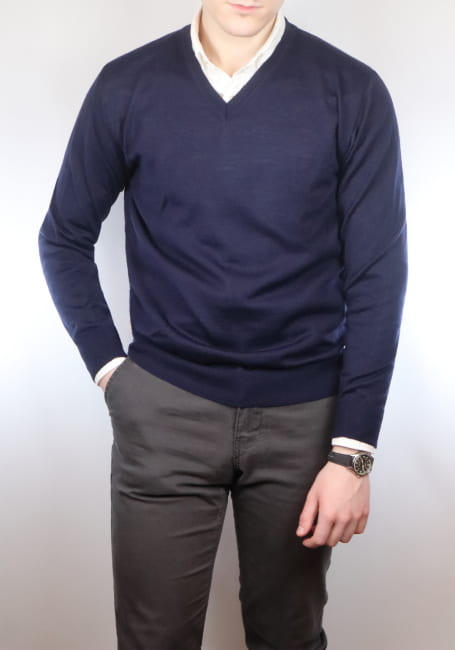 Man wearing a navy v neck jumper and white shirt