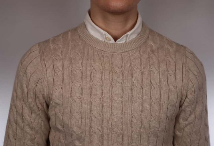 Man wearing a natural cable knit round neck jumper and white shirt combo