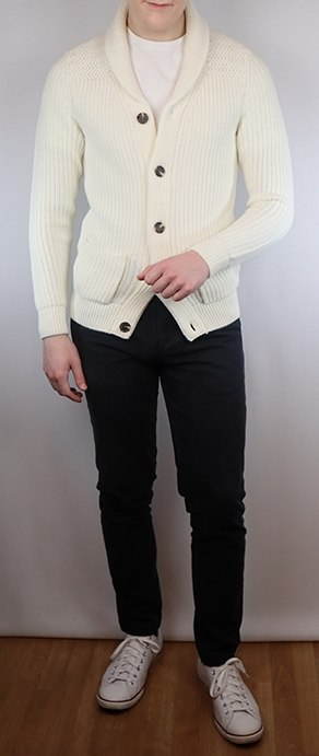Man wearing an ecru shawl sweater with white converse low tops